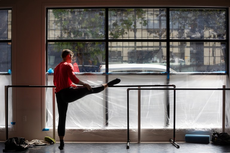 Dancer Peter Kurta of Smuin Contemporary Ballet at the barre facing a window onto the street.