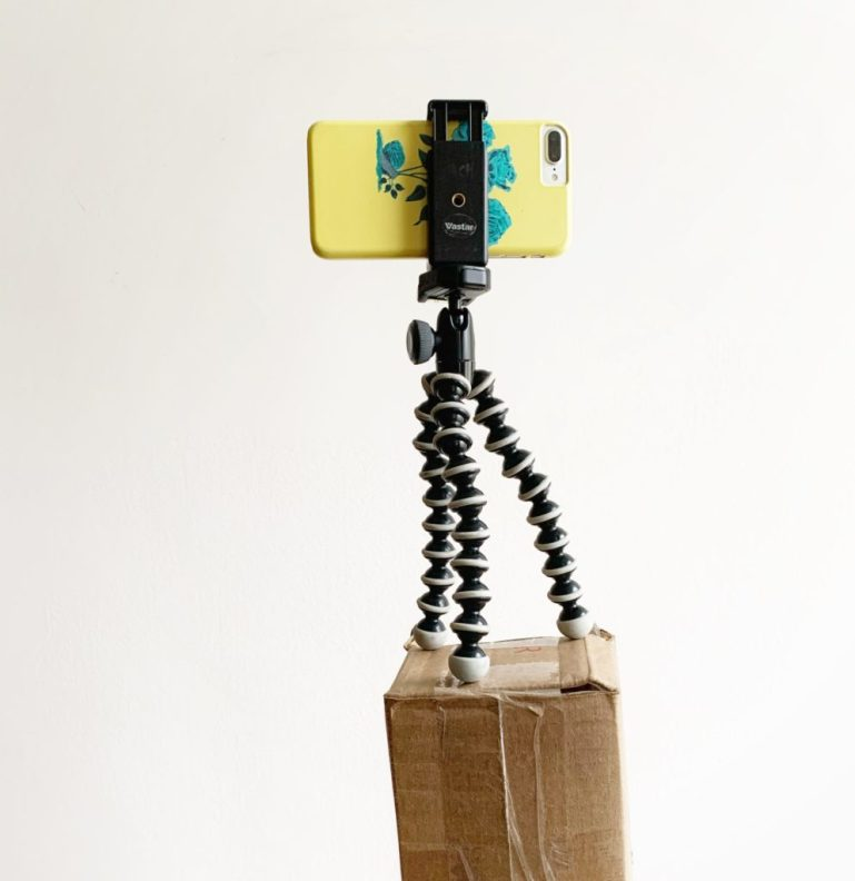 An iPhone on a mini tripod balanced on a box so it's at eye level.