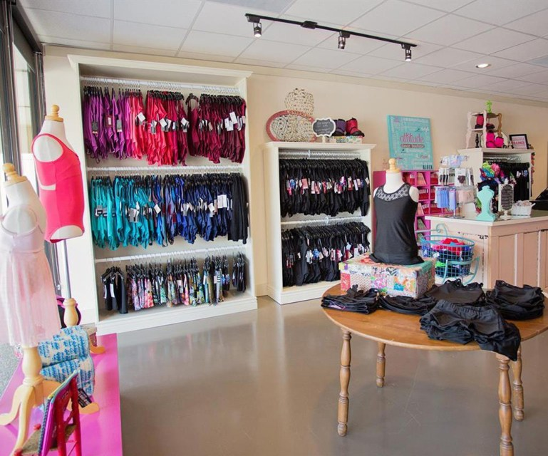 Interior shot of Attitude Dance Boutique in College Station, TX, with color-blocked racks of leotards at back, and a display of classic black on table at front.