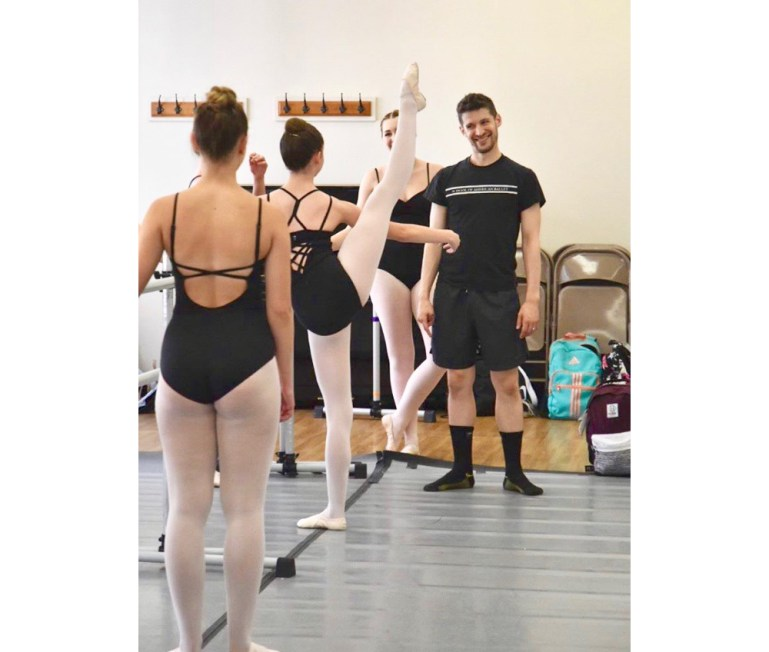 Barry Kerollis, teaching a master class for dancers of LimeLitez Dance Academy, who are at the barre, facing him.