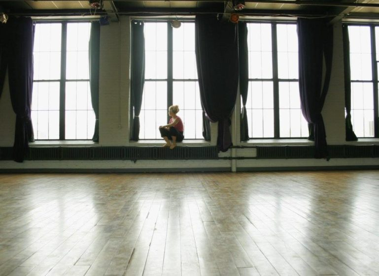Valerie Green, executive director of Dance Entropy Inc, sitting on the window sill of Green Space, her large dance studio with wood floors.