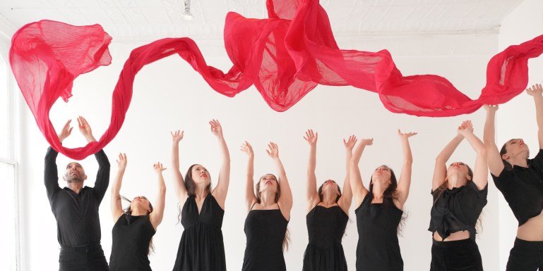 Members of Dance Entropy wearing black and throwing up a long red scarf above them.