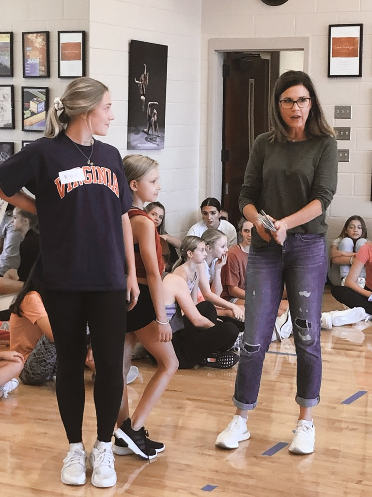 Dancers sitting on the floor during rehearsal with Bellissimo Dance Boutique owner and another woman standing in front of them.