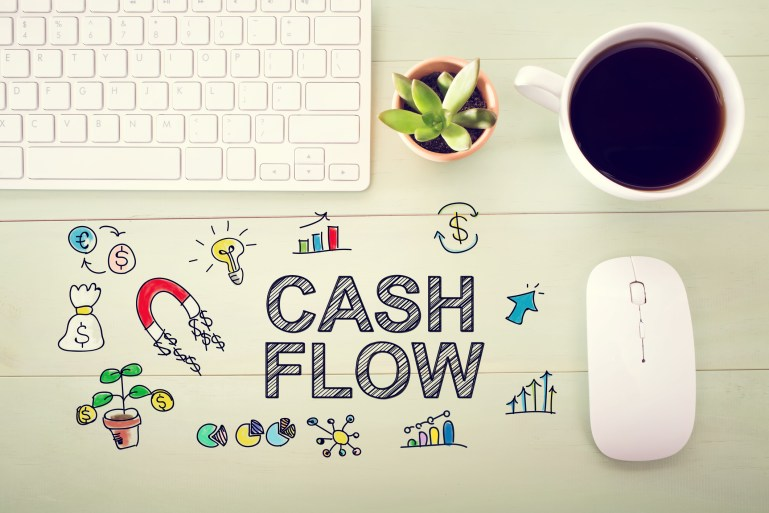 Illustration with words Cash Flow superimposed on desktop with computer keyboard, mouse and cup of coffee.