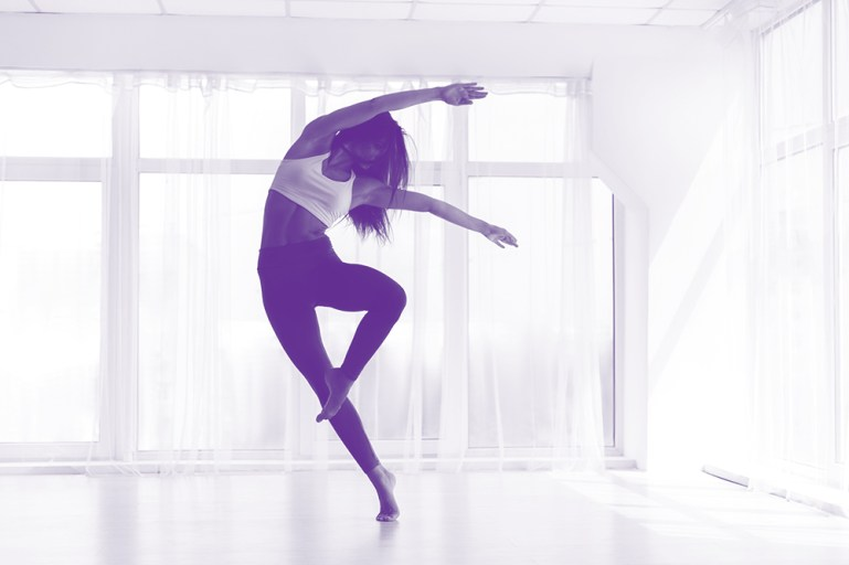 A black and white image, shaded slightly purple, depicting a woman dancing in a light-filled studio.