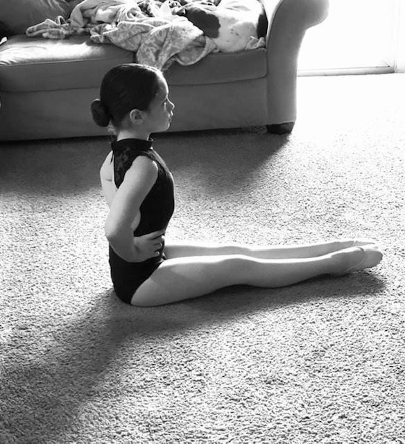 A young girl takes dance class in her living room, wearing a leotard and sitting up very straight with her legs outstretched in front of her