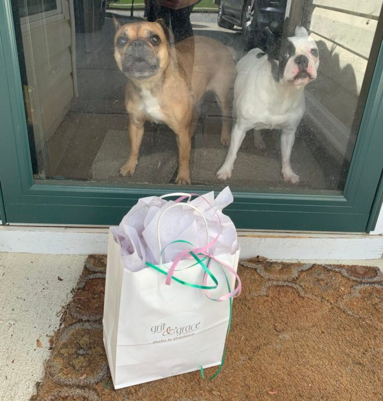 Package from Grit & Grace on doormat of porch with two cute dogs on the other side of the windowed door.