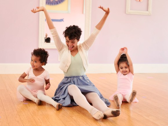 A teacher sits on the floor, arms raised to the sky in delight. She's flanked by two toddler-aged girls who copy her.