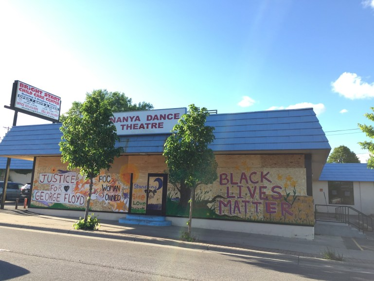 "A boarded up building with a sign–""Ananya Dance Theatre""—on top. The boards have murals saying ""Black Lives Matter,"" ""Justice for George Floyd"" and more."