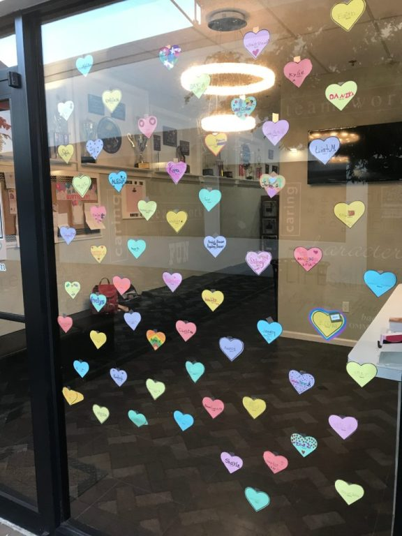 Dozens of colorful paper hearts taped in the window of a dance studio