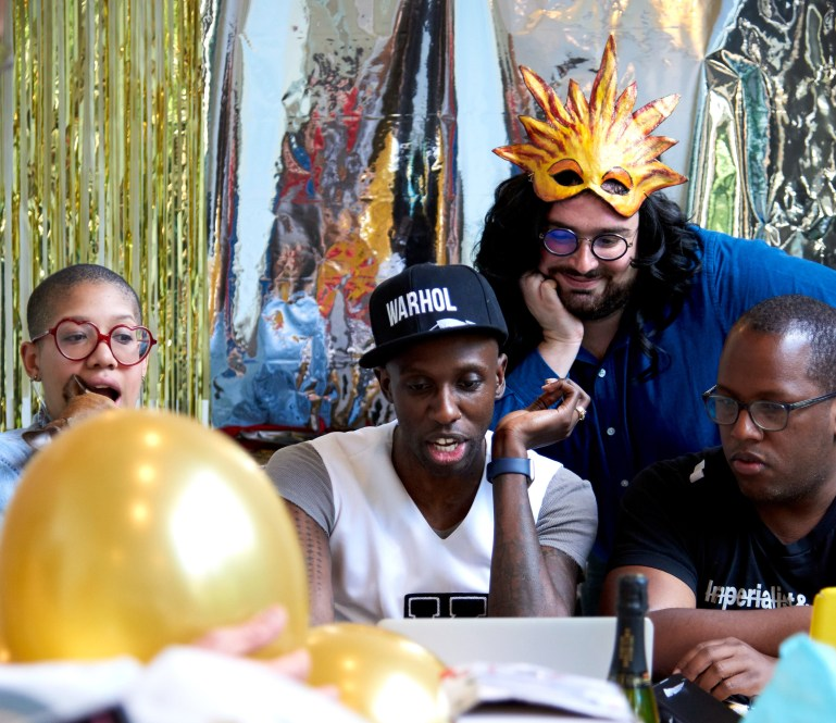 Kelly sits at his computer, surrounded by three people looking over his shoulder. They are surrounded by silver and gold balloons and decorations, and one person wears a gold hat.
