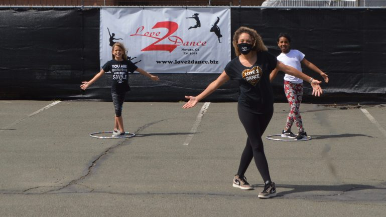 "A teacher, wearing a mask, and two young students pose in a parking lot. There's a ""Love2Dance"" sign in the background, and students are spaced out with hula hoops."