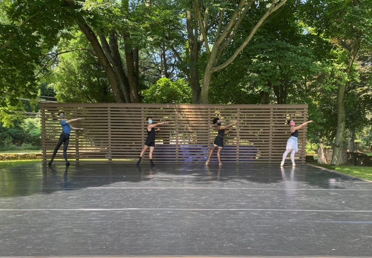 Four teen students–two boys and two girls—take barre on an outdoor stage.