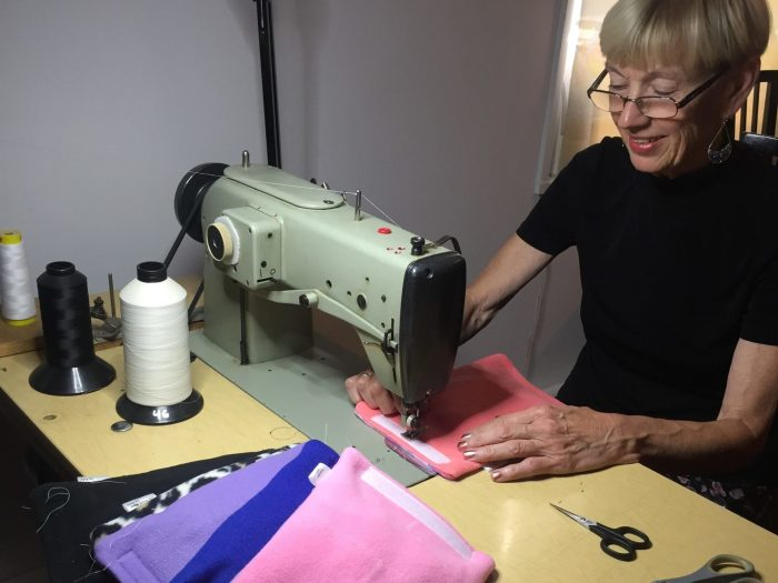 Kathryn Sullivan sitting at an industrial sewing machine sewing her product—The Ballet Glider—in pink, blue, purple fleece material. Scissors on the table.