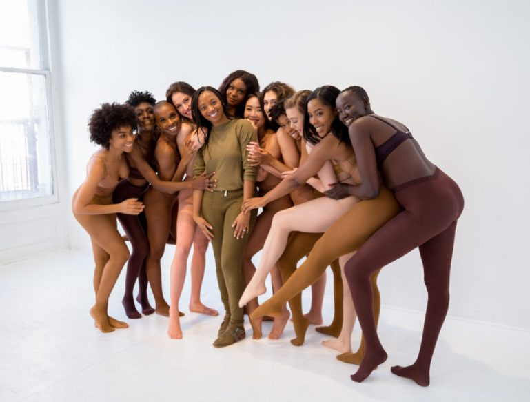 Group of models with various skin tones wearing Nude Barre hosiery and undergarments, with founder and CEO Erin Carpenter at center, dressed in olive shirt and leggings.