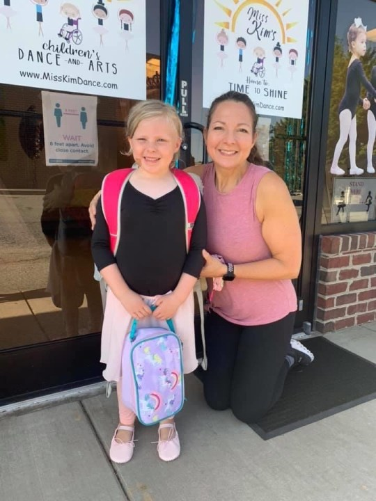 Miss Kim kneels in front of her dance studio next to a young student, both of whom are smiling