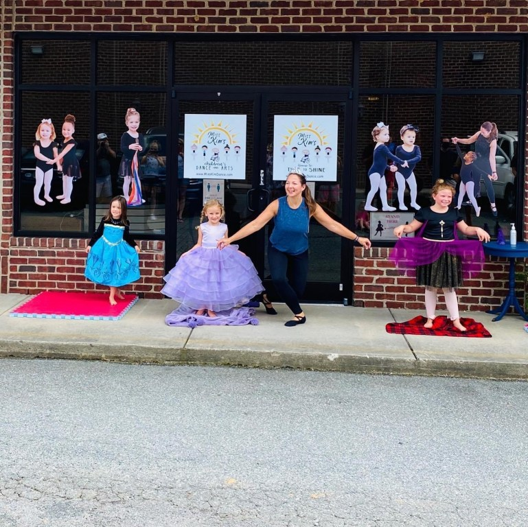Miss Kim curtsies in front of her studio with three young students who wear costumes