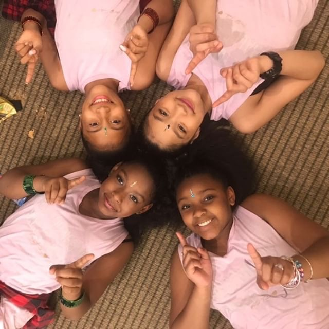 Four girls wearing pink shirts lay on the ground, smiling, with their heads together, make #1 signs with their fingers