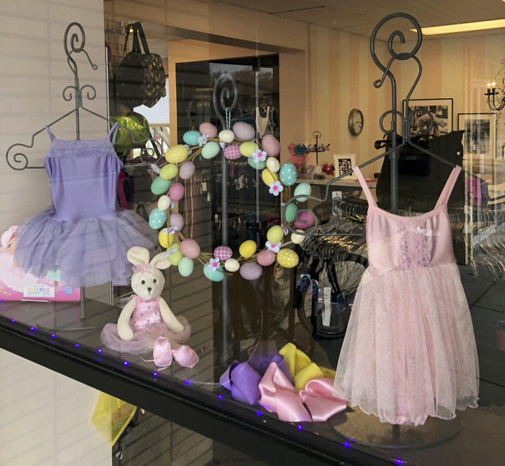 Mauve and pink children's tutus in store window with easter bunny and easter egg wreath.