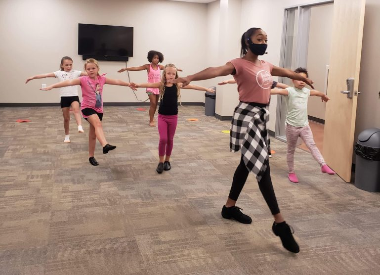 Lisa McCabe, wearing a mask, demonstrates a tendu for six young students