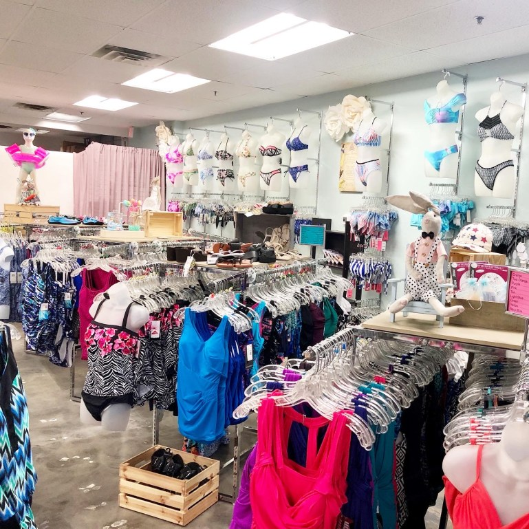 Display wall of bikinis with other swimwear styles on racks in front of it.