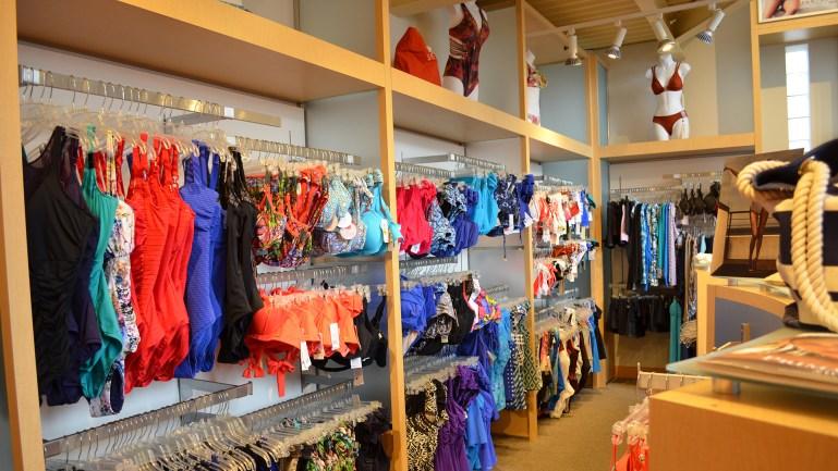 Light wood shelves with racks of colorful swimwear.