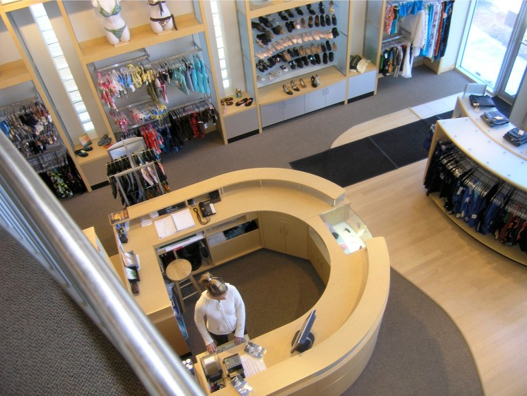 View from the mezzanine at Brio Bodywear, looking down at a U-shaped cash desk and displays of dance shoes.