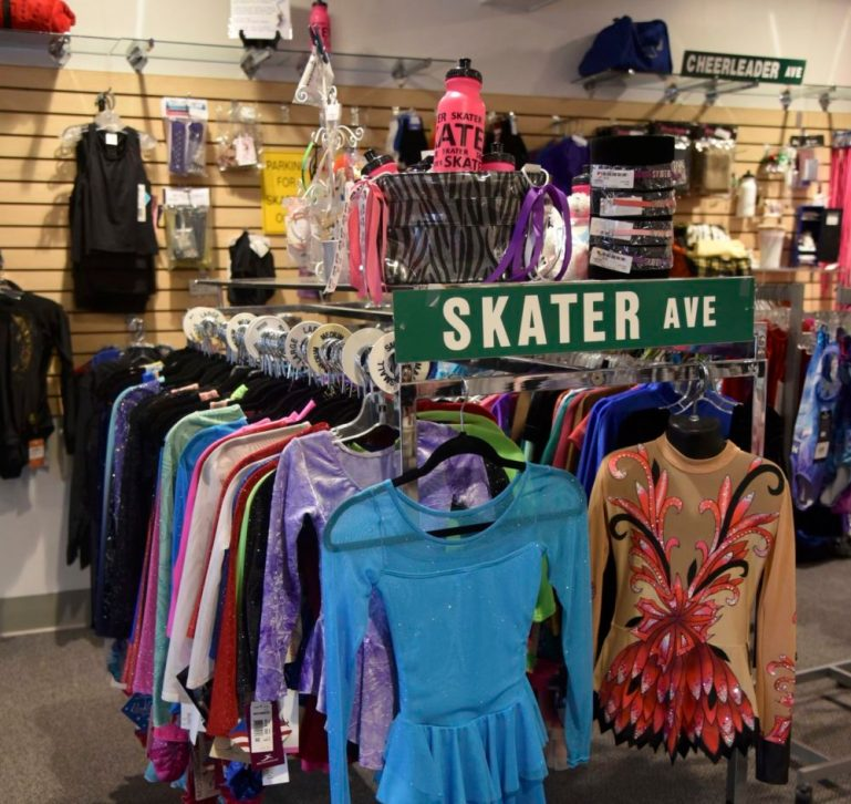 """Rack of skating outfits with a sign """"Skater Ave"""" on it and """"Cheerleader Ave"""" on a wall display behind it."""