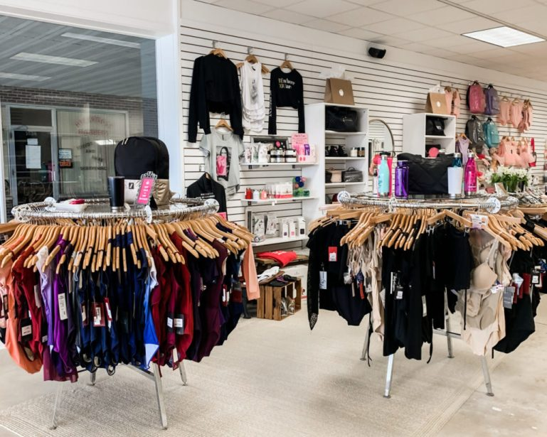 Round racks of dance leotards with slatwall display of dance bags, and other dancewear.