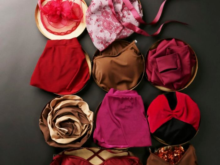 Red, pink, burgundy dance leotards and skirts arranged in round boxes, as if it was a box of chocolates.