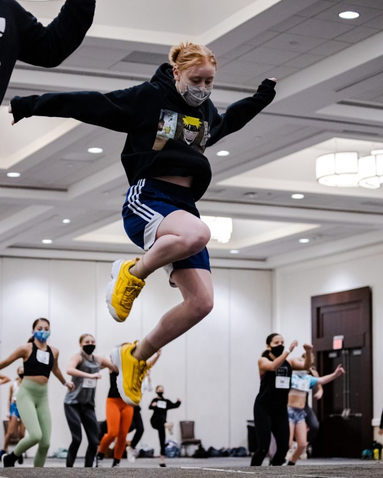 A redheaded convention assistant wearing yellow sneakers, blue shorts, a black graphic sweatshirt and a mask jumps on a stage, with convention attendees dancing behind her