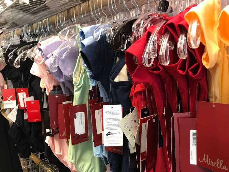 A rack of solid-colored leotards in various colors