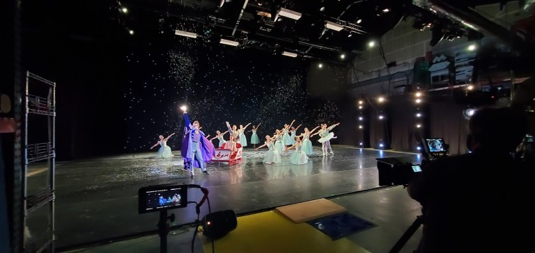 Two cameras film the snow scene of the Nutcracker onstage, which we see from a distance—dancers in light blue tutus, Clara being pulled in a sleigh by Drosselmeier, and snow falling from the sky