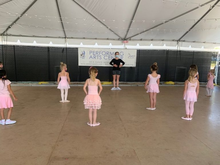 A woman in a mask, sneakers, grey shorts and a black t shirt demonstrates first position to a class of young girls in pink outfits in the outdoor tent