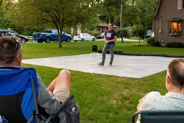 Sofranko, wearing jeans and a Grand Rapids Ballet tshirt, stands on a makeshift stage in a grassy backyard, speaking to patrons who sit in lawn chairs
