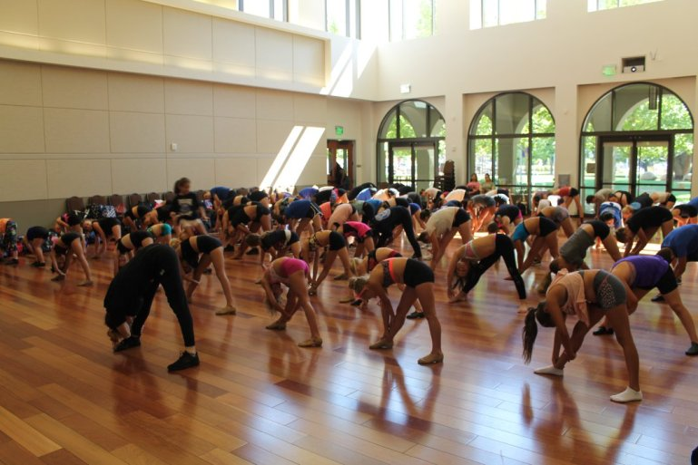 A large group of students stretch in a convention-style space with large windows. They follow a teacher at the front of the room in leaning over their right leg for a hamstring stretch