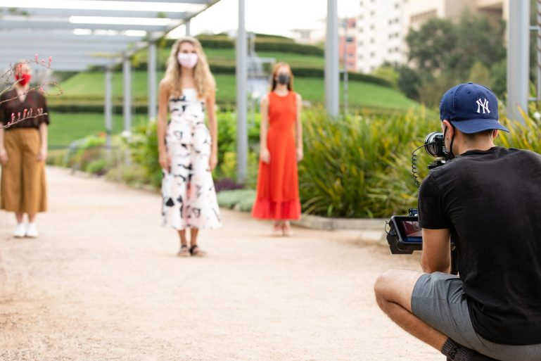 Three Houston Ballet dancers, all white women, stand in a garden, facing a man who is squatting and holding a camera. They are all masked, and the women wear bright, summery clothing.