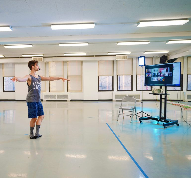 Barry Kerollis demonstrates a pirouette preparation from fifth position in an empty studio. He faces a large monitor showing Zoom screens.