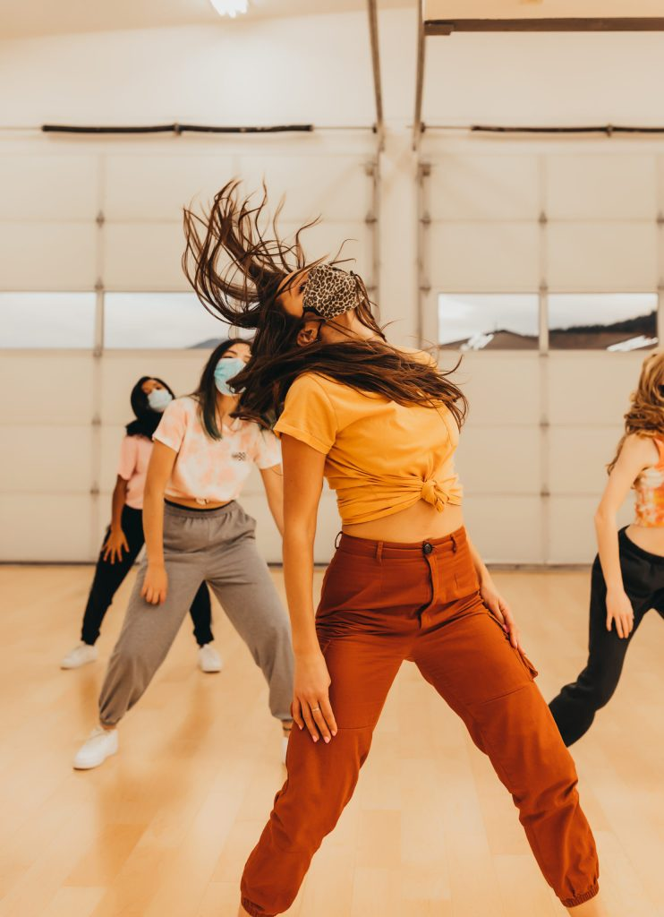 Masked dancers in bright colors dance in Nika Kermani's new studio. The garage doors are closed behind them. The young woman in the front throws her head backwards, her hair dramatically flipping back.