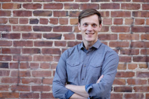 Ben Henry-Moreland, a young white man, wears a blue button-down shirt. He crosses his arms and smiles against a brick wall backdrop.
