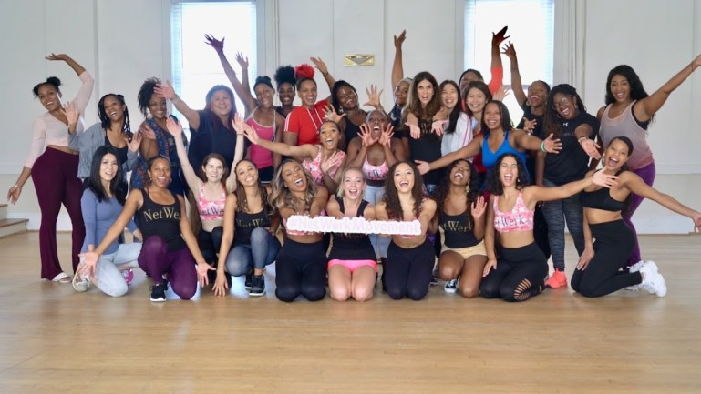A group of around 30 women, mostly women of color, pose together in a group. They are in a dance studio, and wear athleisure. They hold a sign but it's hard to read with the camera flash.