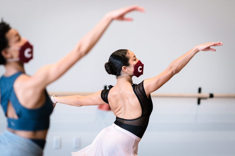 "Two dancers, both wearing red masks with a ""C"" for Collage on them, dance in a white-walled studio. Their arms are in first arabesque."