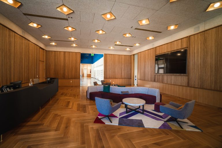 The lobby of Collage's new building, with colorful, trendy furniture, sleek overhead lighting, a front desk, a tv and wood paneled walls.