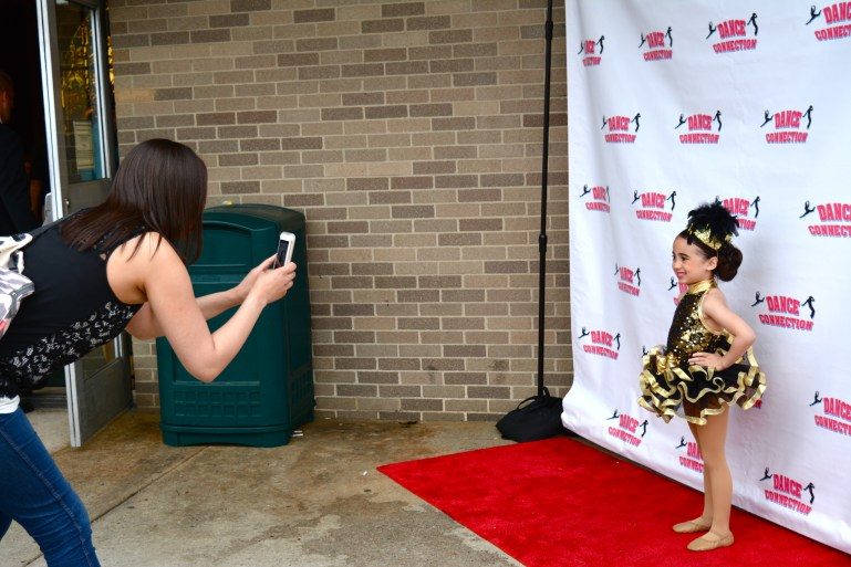 A young dancer in a black and gold costume has her photo taken on the Dance Connection red carpet