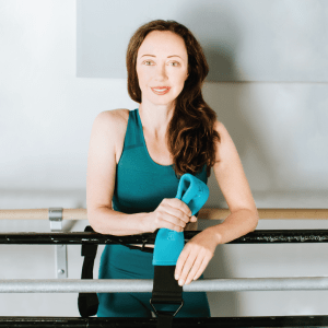Aleksandra Efimova, a white woman with long brown hair, leans over a ballet barre, holding a blue band in her hands. She wears a teal shirt and there is a white wall with more barres behind her.