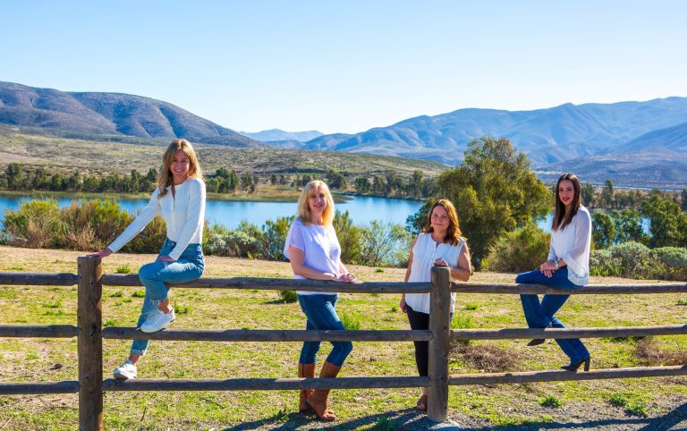 Neisha Hernandez, Kaylee Kiff, Franchesca Gonzalez Otañez and Melissa Treziok pose on a wooden fence overlooking beautiful lake and some mountains. They each wear white blouses and jeans.