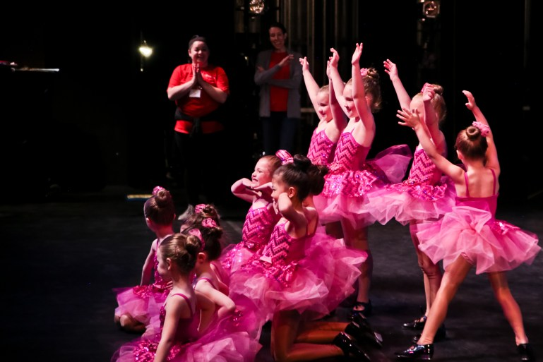 A group of ten young girls pose for a photograph, wearing pink sequined costumes and tap shoes.