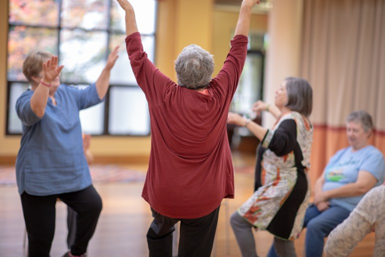 A group of older women dance with their arms raised, as several other look on from chairs. They are in a large room with a big window, with a blurred tree in the background.
