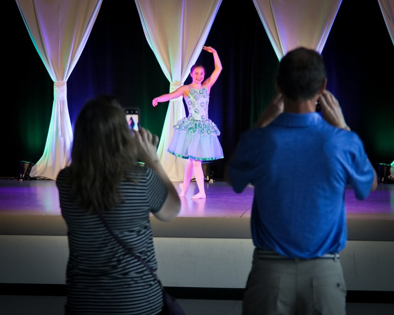 A middle school aged dancer performs a solo in a blue ballet costume with a long tutu. Two adults stand in front of the stage, taking photos or videos of her.