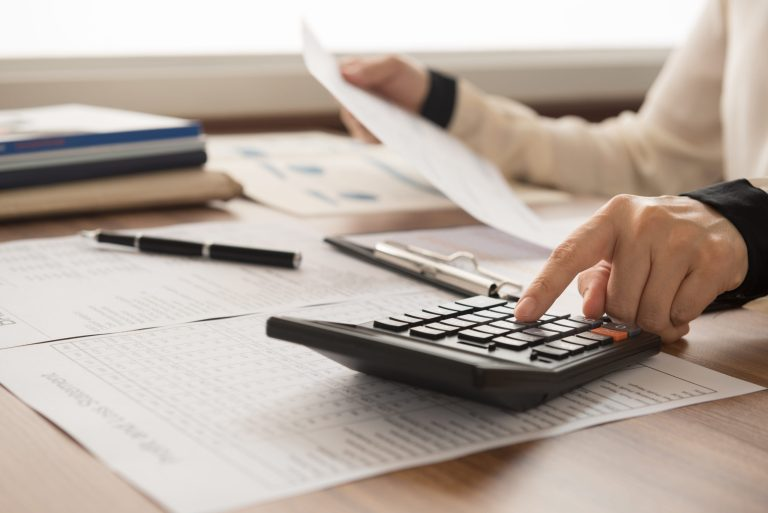 A stock image of a woman's hands using a calculator, with lots of papers scattered on a table